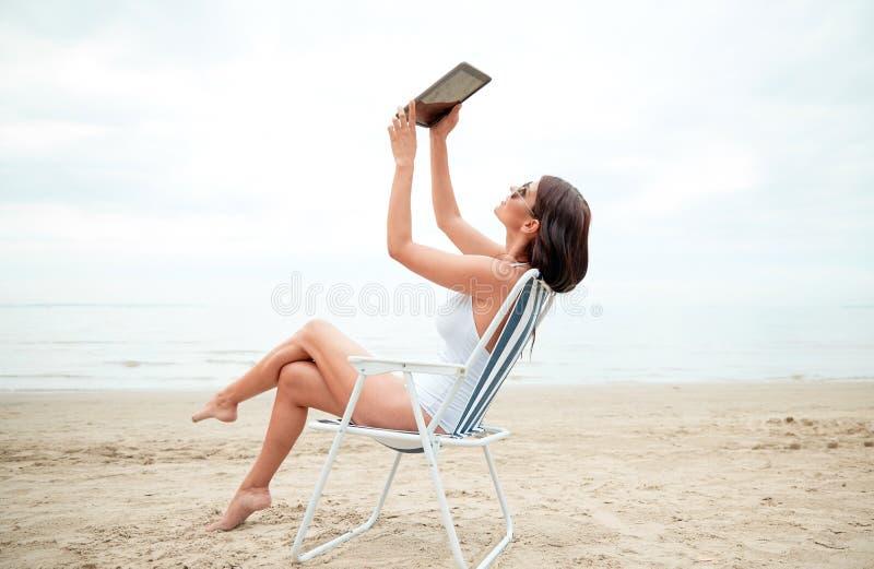 Mujer feliz con la PC de la tableta que toma el selfie en la playa imágenes de archivo libres de regalías