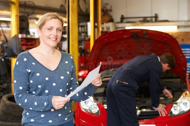 Mujer feliz con la reparación Bill del garaje fotografía de archivo