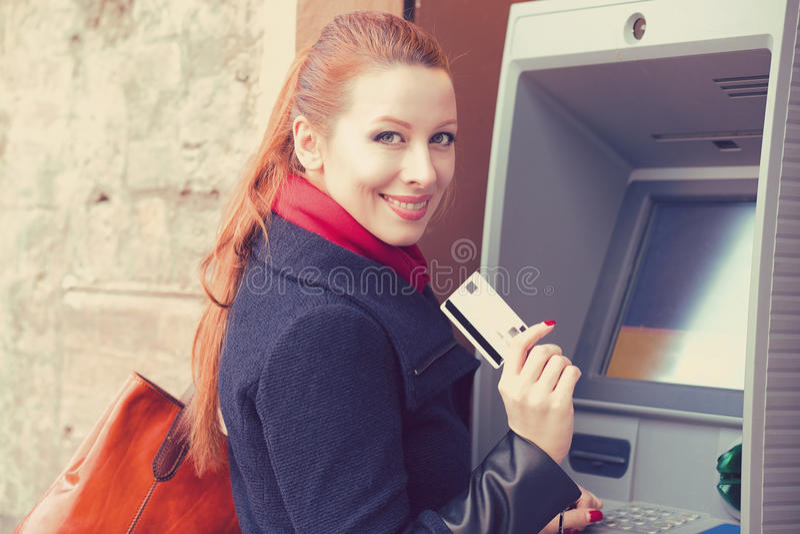 Mujer feliz con la tarjeta de banco usando la atmósfera fotografía de archivo libre de regalías