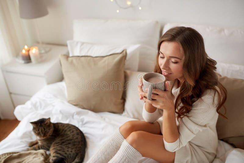 Mujer feliz con la taza de café en cama en casa fotografía de archivo