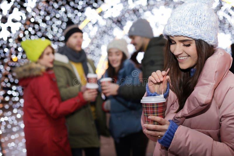 Mujer feliz con la taza de vino reflexionado sobre y de amigos en la feria del invierno imagenes de archivo