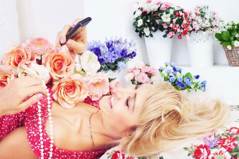 Mujer feliz con las flores que mandan un SMS al mensaje en el teléfono imagen de archivo libre de regalías
