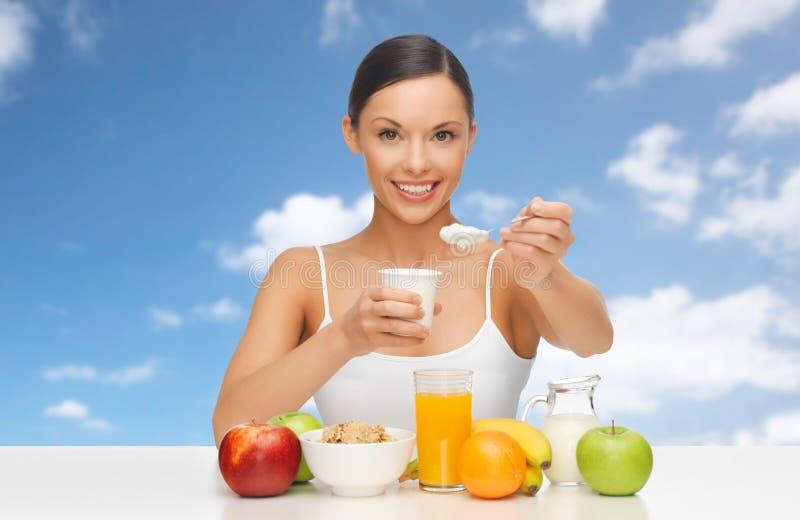 Mujer feliz con las frutas, cereales comiendo el yogur imagen de archivo libre de regalías