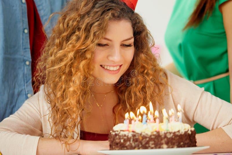 Mujer feliz con las velas en la torta de cumpleaños en el partido fotografía de archivo