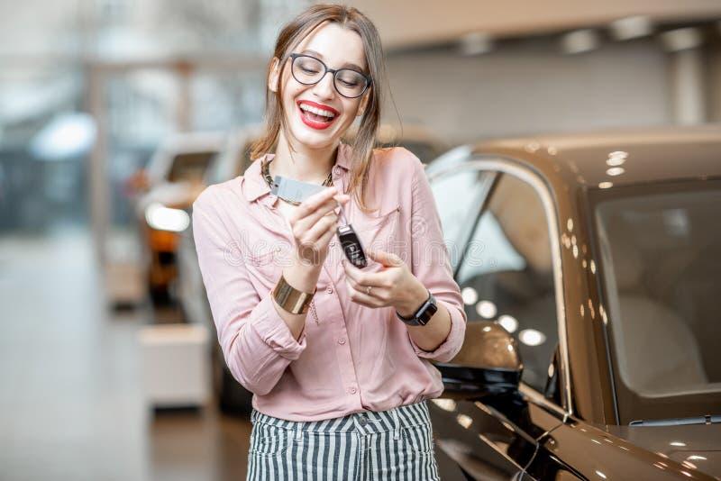 Mujer feliz con llaves en la sala de exposición del coche fotos de archivo libres de regalías