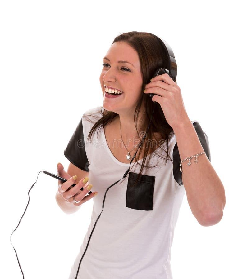 Mujer feliz con los auriculares que escucha la música fotografía de archivo