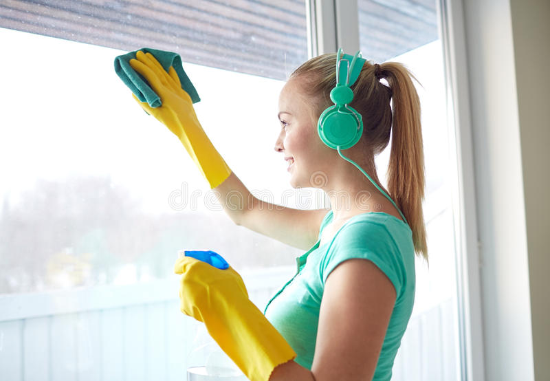 Mujer feliz con los auriculares que limpian la ventana imágenes de archivo libres de regalías
