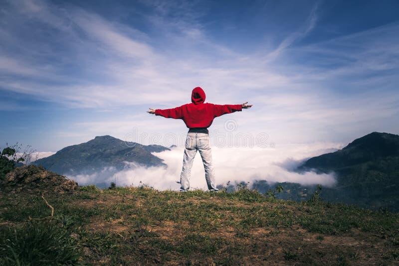 Mujer feliz con los brazos abiertos permanecer en el pico del borde del acantilado de la montaña debajo del cielo ligero que goza foto de archivo