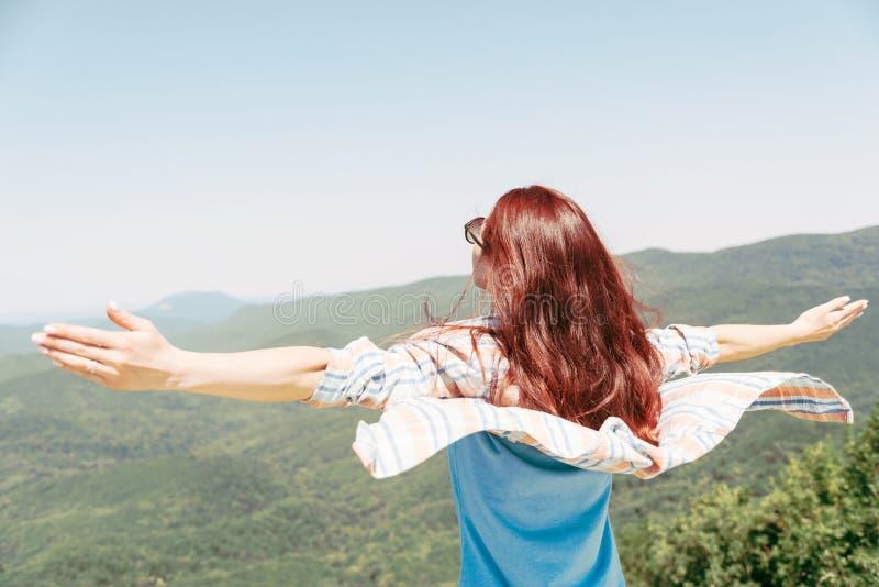 Mujer feliz con los brazos aumentados altos en montañas imágenes de archivo libres de regalías