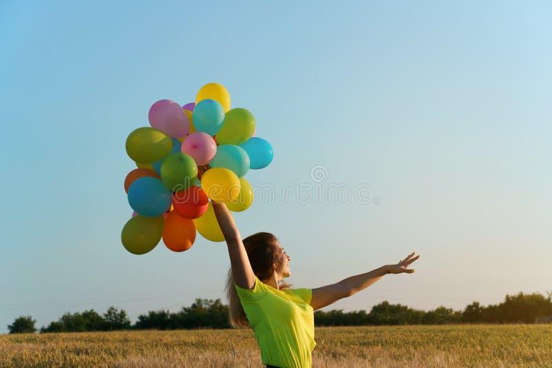 Mujer feliz con los globos en la puesta del sol en verano fotos de archivo