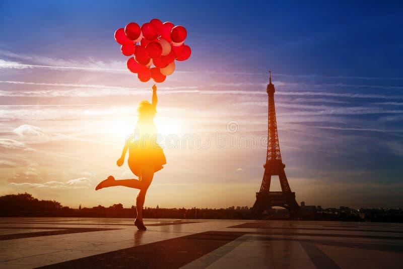 Mujer feliz con los globos rojos que saltan cerca de torre Eiffel en París foto de archivo