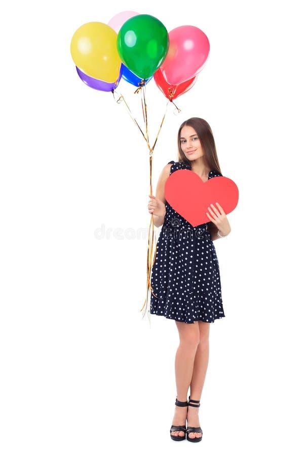 Mujer feliz con los globos y el corazón rojo imagenes de archivo