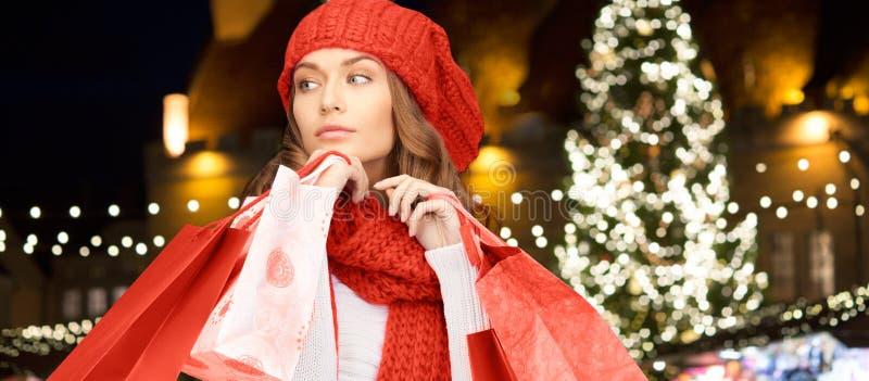 Mujer feliz con los panieres sobre el árbol de navidad fotos de archivo libres de regalías
