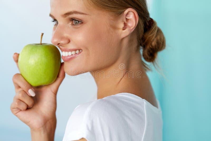 Mujer feliz con sonrisa hermosa, dientes sanos que sostienen Apple fotografía de archivo libre de regalías