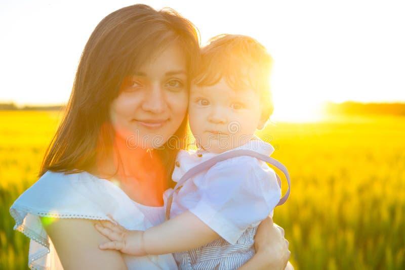 Mujer feliz con su bebé el día soleado del verano fotografía de archivo libre de regalías