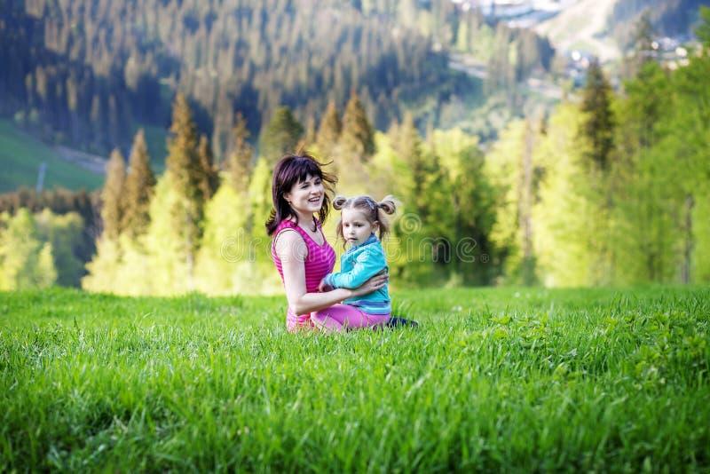 Mujer feliz con un bebé que juega encima de la montaña El concentrado imagen de archivo libre de regalías