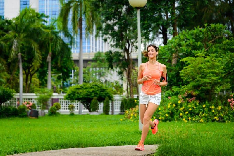 Mujer feliz de la aptitud que corre en el parque de la ciudad fotos de archivo libres de regalías