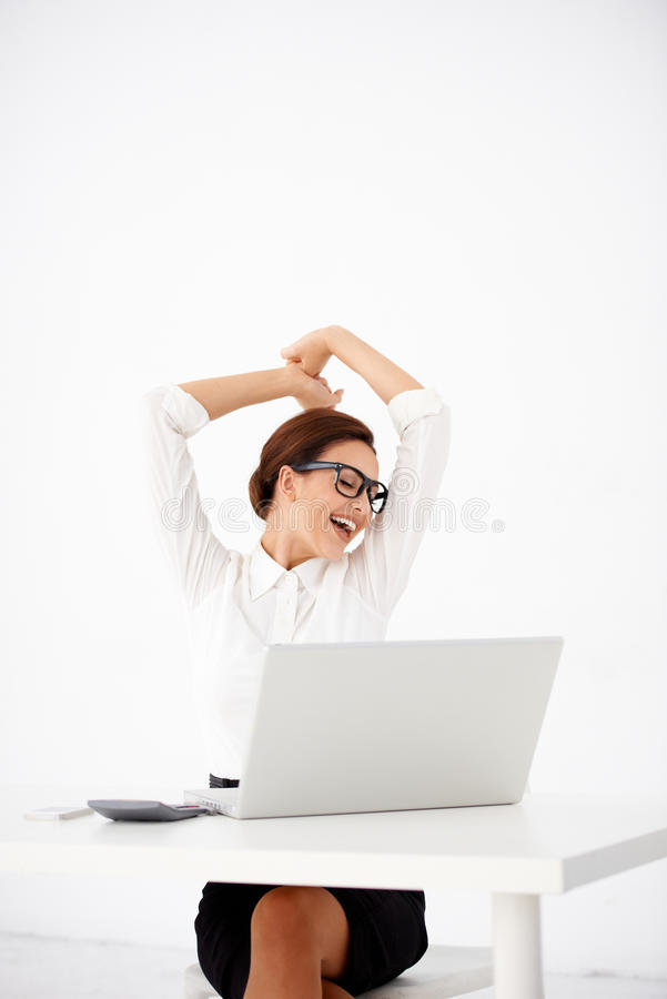 Mujer feliz de la oficina que estira en frente su ordenador portátil imagen de archivo libre de regalías
