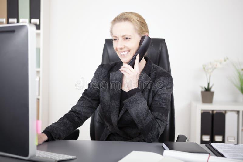 Mujer feliz de la oficina que habla con alguien en el teléfono foto de archivo