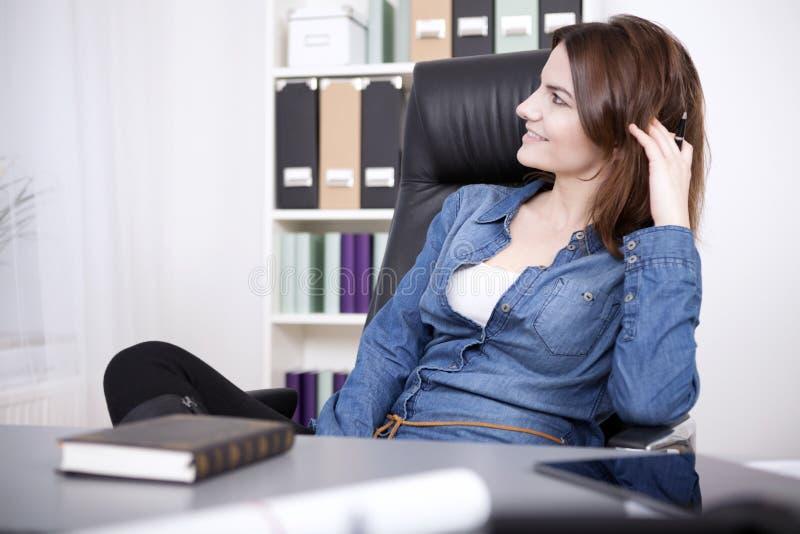 Mujer feliz de la oficina que se relaja en silla en la oficina imagenes de archivo