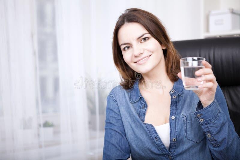 Mujer feliz de la oficina que sostiene un vidrio de agua fotografía de archivo libre de regalías