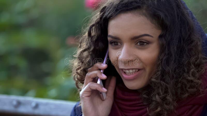 Mujer feliz de la raza mixta que habla sobre smartphone al aire libre, sonriendo sinceramente imagenes de archivo