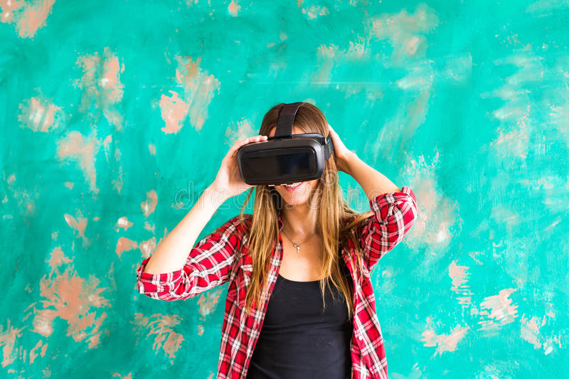 Mujer feliz de la sonrisa que consigue experiencia usando los vidrios de las VR-auriculares de realidad virtual en casa muchas la foto de archivo
