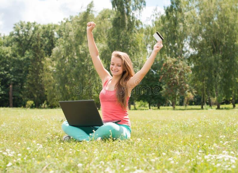 Mujer feliz de las compras de Internet en línea con el ordenador portátil y sentarse de la tarjeta de crédito al aire libre en hi fotografía de archivo