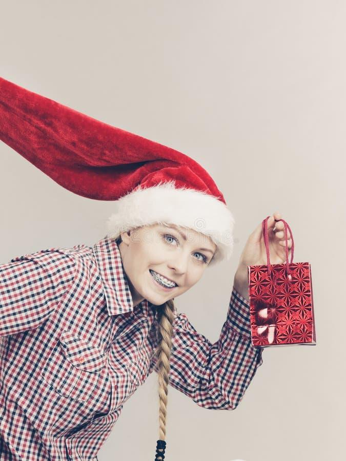 Mujer feliz de las compras que lleva el sombrero de Papá Noel foto de archivo libre de regalías