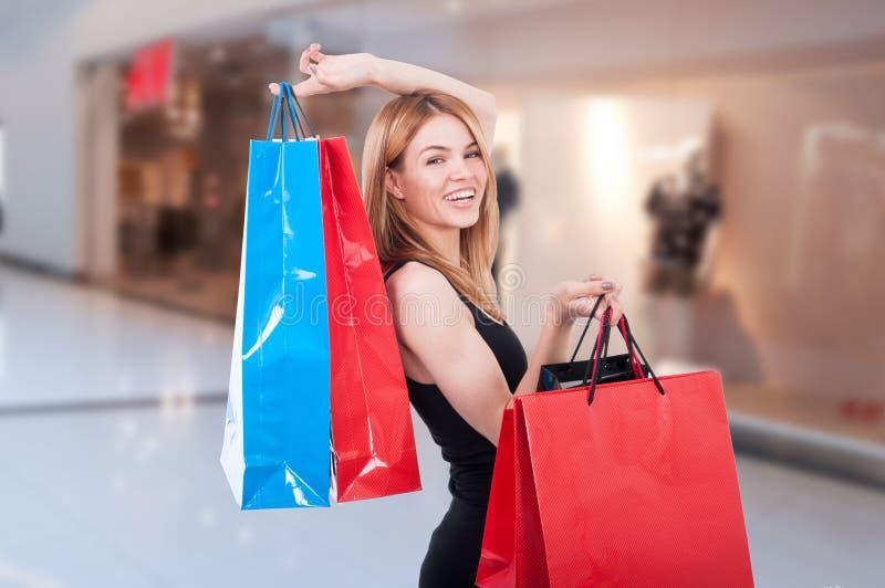 Mujer feliz de las compras que sostiene bolsos en la alameda fotos de archivo libres de regalías