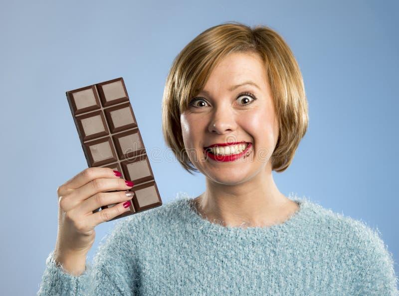 Mujer feliz del adicto al chocolate que sostiene la boca grande de la barra expresión emocionada manchada y loca de la cara imágenes de archivo libres de regalías