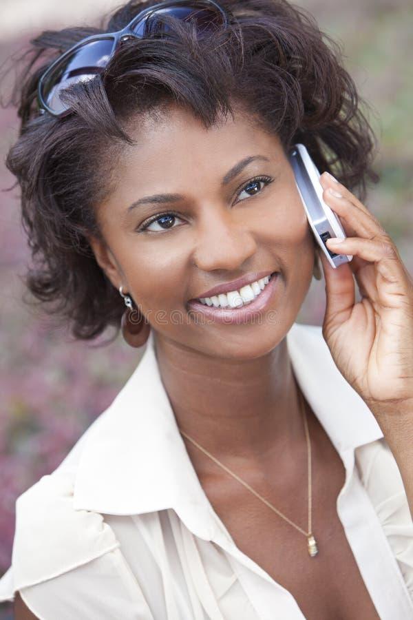 Mujer feliz del afroamericano que habla en el teléfono celular imagen de archivo libre de regalías