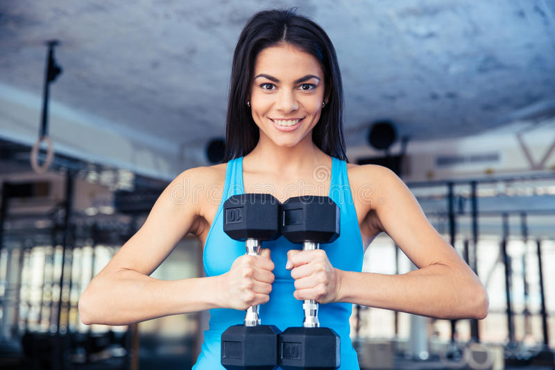 Mujer feliz del ajuste que lleva a cabo pesas de gimnasia imágenes de archivo libres de regalías