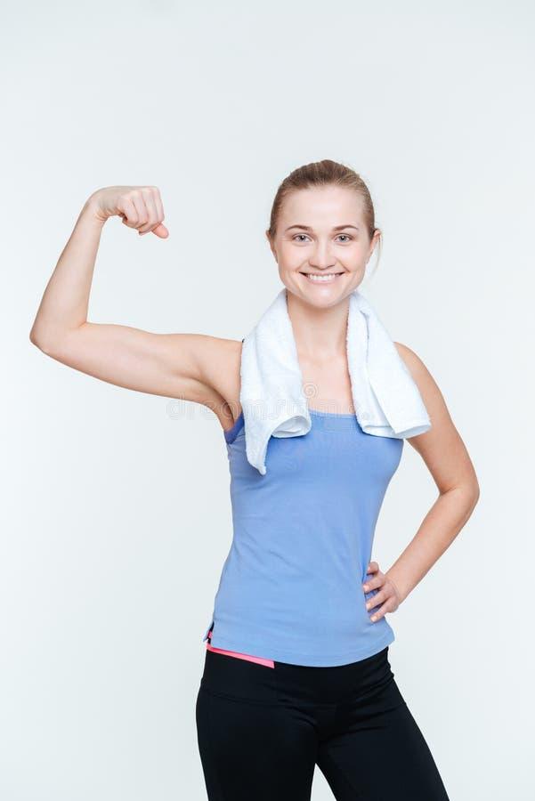 Mujer feliz del ajuste que muestra su bíceps fotografía de archivo libre de regalías