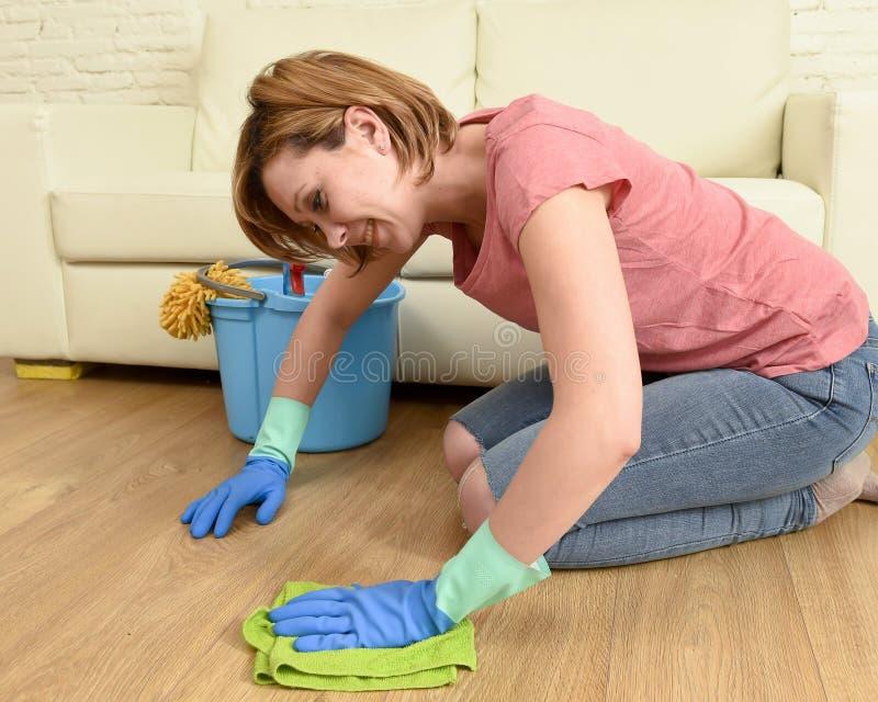 Mujer feliz del ama de casa con el arrodillamiento del piso de la sonrisa que se lava de la casa hermosa de la limpieza foto de archivo libre de regalías