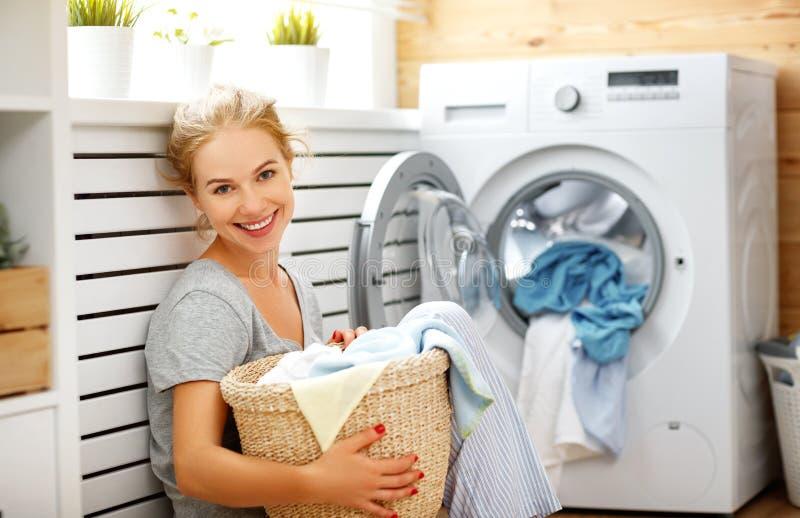 Mujer feliz del ama de casa en lavadero con la lavadora fotografía de archivo libre de regalías
