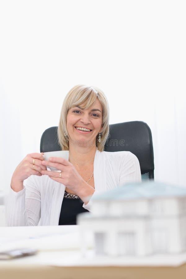 Mujer feliz del arquitecto que tiene descanso para tomar café imágenes de archivo libres de regalías