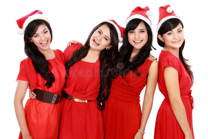 Mujer feliz del asiático de los jóvenes cuatro con el sombrero de santa de la Navidad foto de archivo