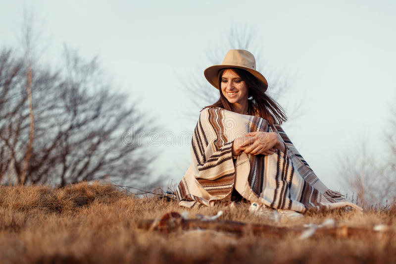 Mujer feliz del boho que se sienta en la puesta del sol en montañas, sombrero que lleva y fotos de archivo