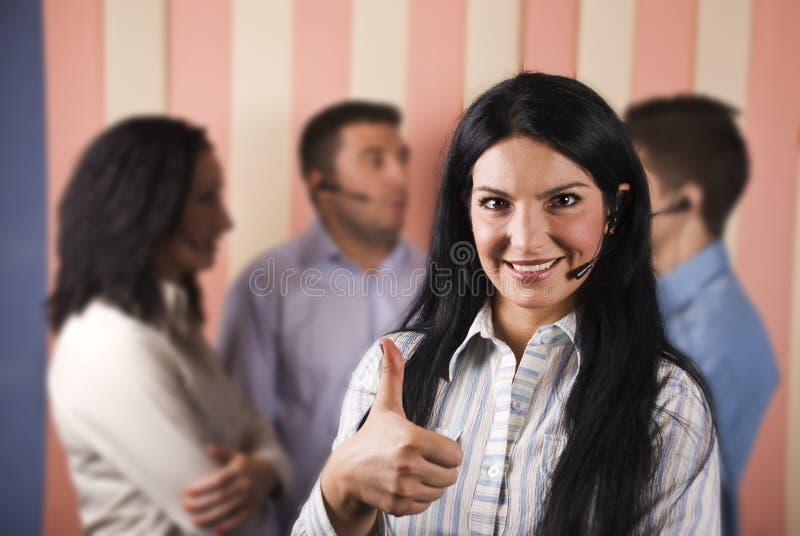 Mujer feliz del centro de atención telefónica que da los pulgares para arriba foto de archivo