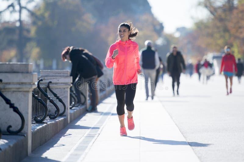 Mujer feliz del corredor en funcionamiento de la ropa de deportes del otoño o del invierno y tr fotografía de archivo libre de regalías