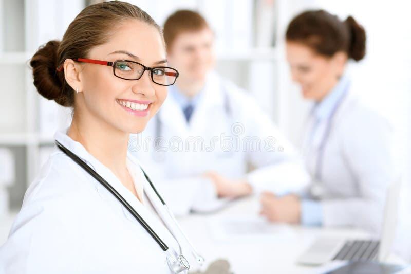 Mujer feliz del doctor con el personal médico en el hospital que se sienta en la tabla Vidrios rojos del marco foto de archivo libre de regalías