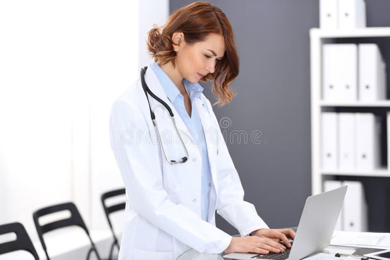 Mujer feliz del doctor en el trabajo Retrato del médico de sexo femenino que usa el ordenador portátil mientras que coloca el mos fotos de archivo