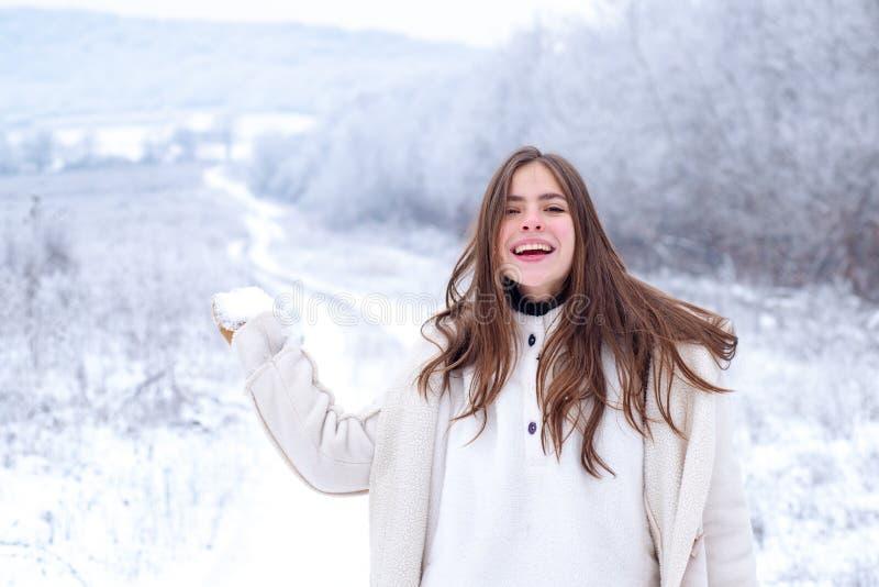 Mujer feliz del invierno encendido en fondo nevoso outdoors Mujer joven de la belleza alegre que se divierte en parque del invier imagen de archivo