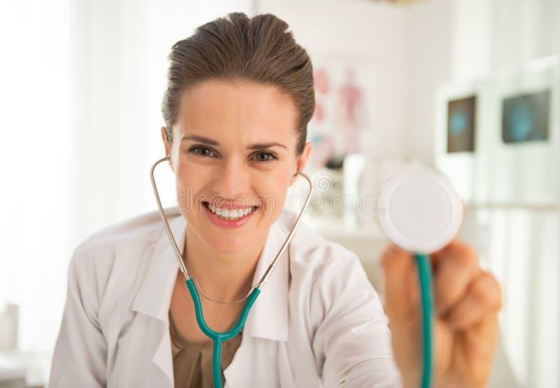 Mujer feliz del médico que estira el estetoscopio imagen de archivo
