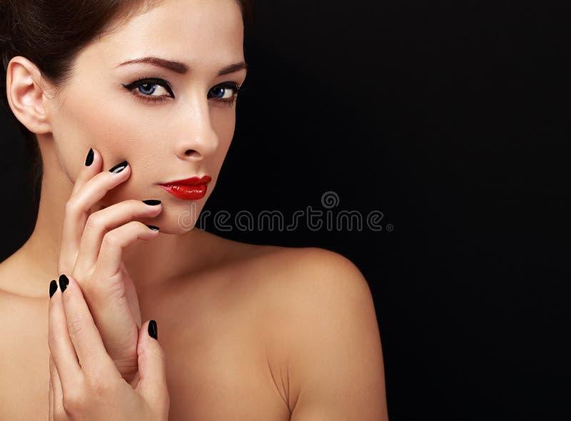 Mujer feliz del maquillaje que mira con los labios rojos y los fingeres negros en negro foto de archivo libre de regalías