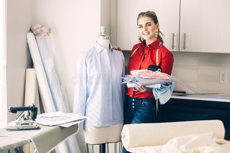 Mujer feliz del sastre con nuevas ropa y herramientas del sastre en su taller del estudio del diseño foto de archivo