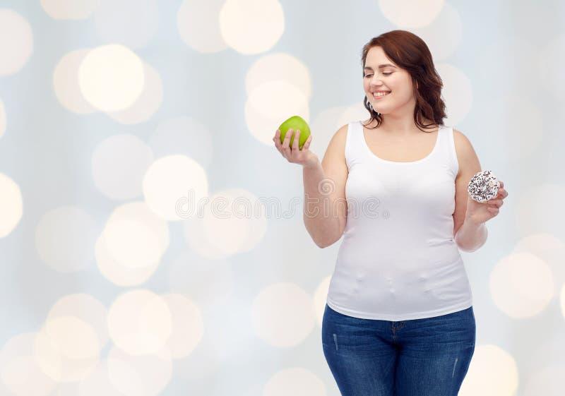 Mujer feliz del tamaño extra grande que elige la manzana o el buñuelo foto de archivo libre de regalías