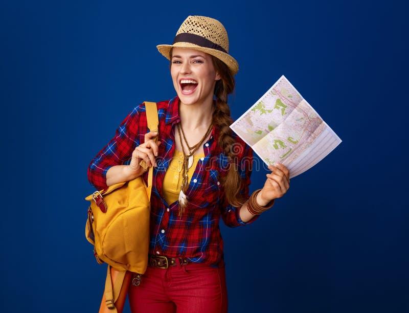 Mujer feliz del viajero aislada en fondo azul con el mapa imagen de archivo