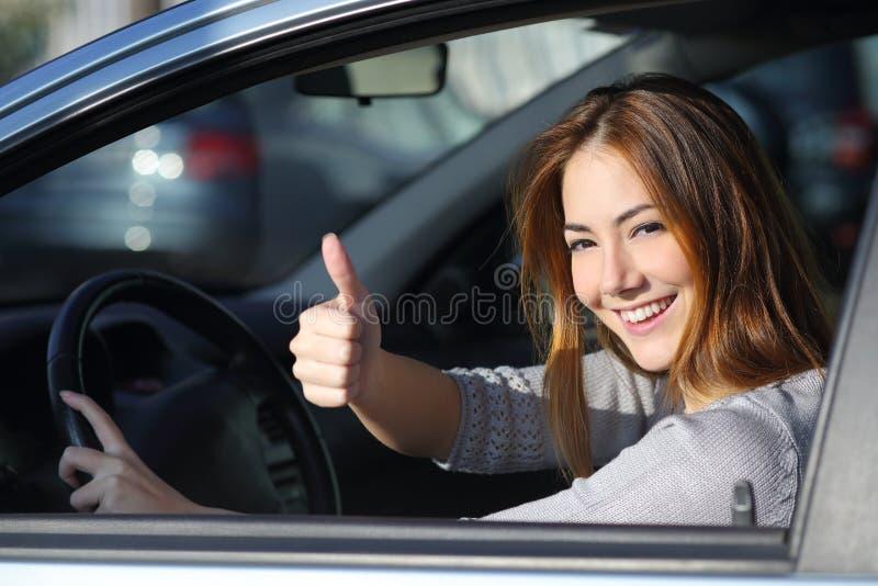 Mujer feliz dentro de un coche que gesticula el pulgar para arriba imágenes de archivo libres de regalías